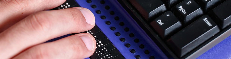 Imagem Cego pessoa usando computador com a informação em braille computador