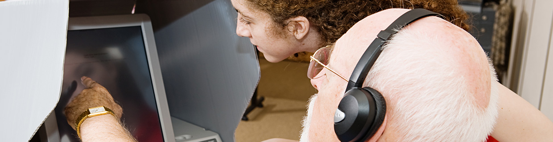 Foto de Sénior em formação tendo o auxilio da formadora junto ao computador