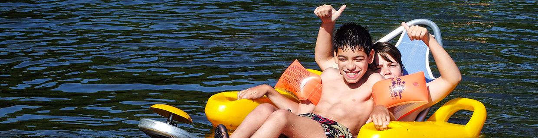 Imagem com duas pessoas na praia Fluvial utilizando o tiralô