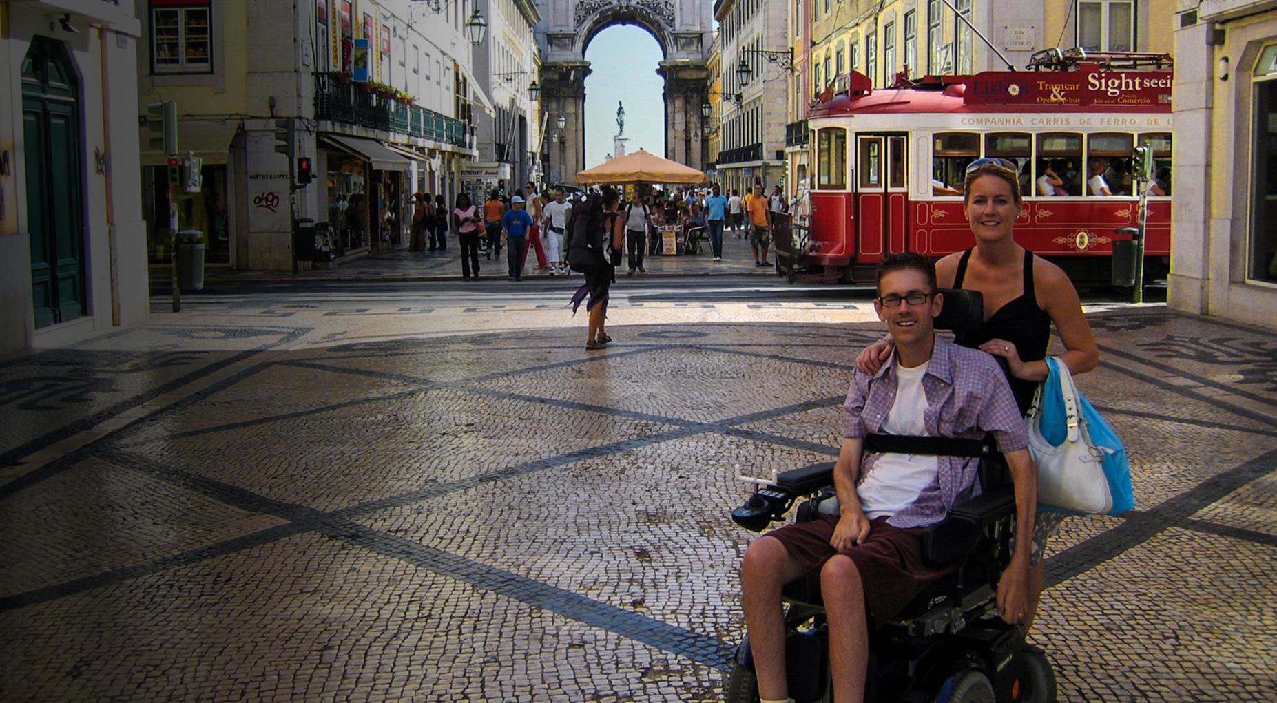 Vista da Rua Augusta na Baixa de Lisboa com duas pessoas, uma das quais em cadeira de rodas